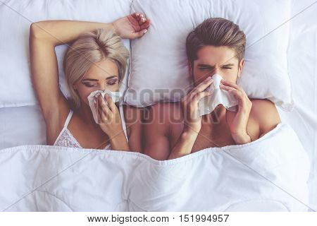 Top view of beautiful young couple wiping noses while lying in bed