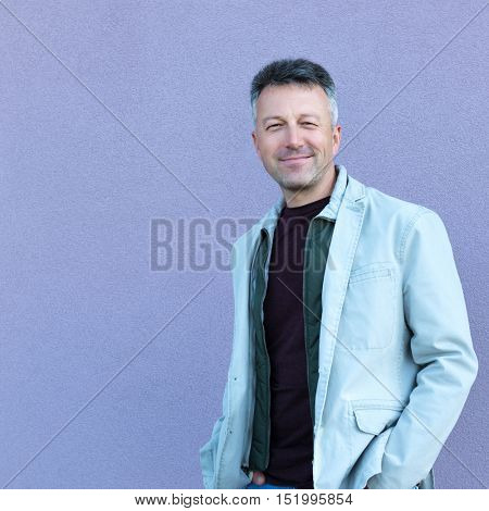 Handsome cheerful mid adult man posing over violet wall. Outdoor male portrait.