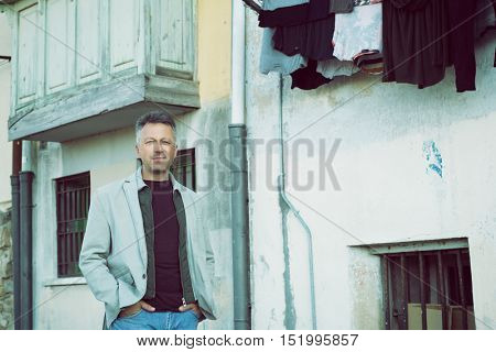 Handsome cheerful mid adult man posing over old house. Outdoor male portrait, image toned.
