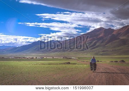 Solo female cyclist on the bicycle on the remote gravel road near Lake Manasarovar in Tibet