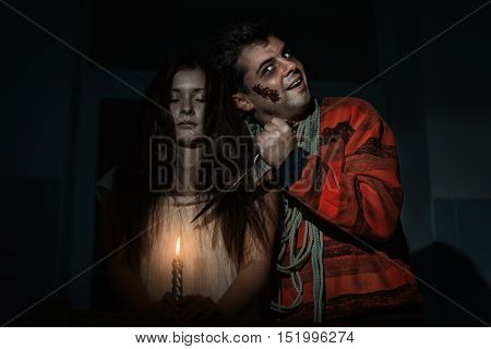 Creepy man and woman are standing in the room he had a knife and weighs a rope around his neck.