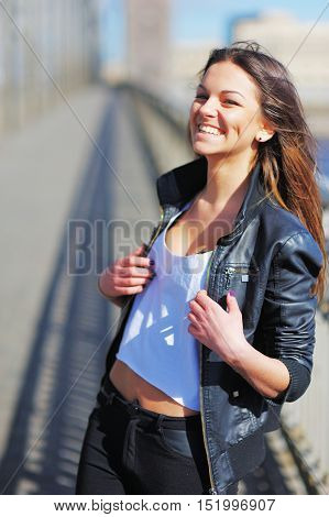 Beautiful young woman in a short t-shirt and leather jacket walks along the waterfront of the St. Petersburg channel happily and laughing merrily.