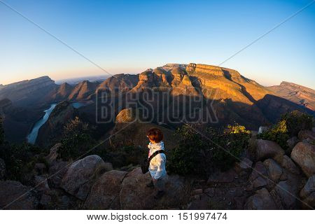 Blyde River Canyon famous travel destination in South Africa. Tourist looking at panorama at sunset. Last sunlight on the mountain ridges. Fisheye distorted view from above.