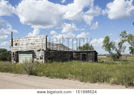 horizontal image of a very old garage no longer in use under a blue sky with white clouds in the summer time.