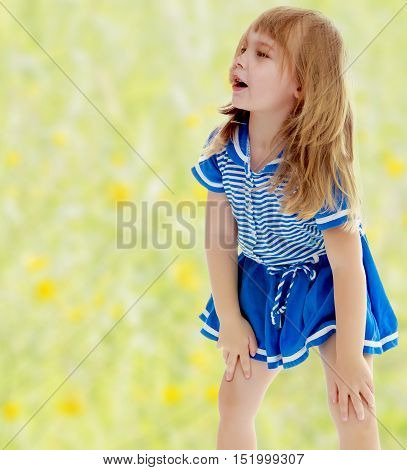 The concept of changing seasons in the life of a child. Yellow green blurred background. Cute little unkempt girl in a short blue dress. Girl looking to the side with his hands on his knees.