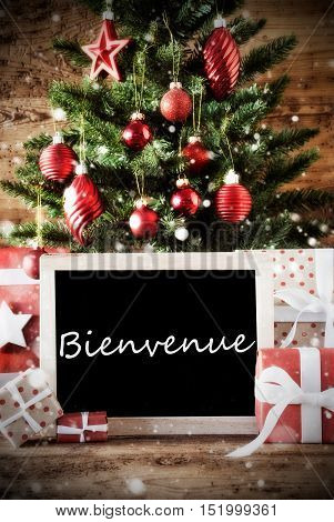 Christmas Card For Seasons Greetings. Christmas Tree With Balls. Gifts Or Presents In The Front Of Wooden Background. Chalkboard With French Text Bienvenue Means Welcome