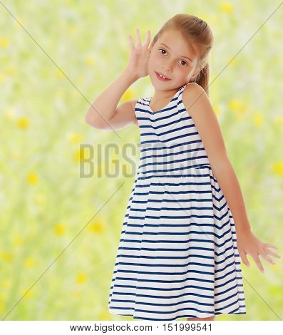 Caucasian little girl in a striped summer dress, listening. Girl holding a hand to his ear.On the background of green grass. The concept of a family holiday.