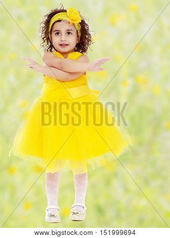 Happy little curly girl in a bright yellow dress, enthusiastically waving his arms.Bright, floral yellow-green blurred background.
