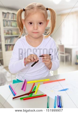 The concept of family happiness, and preschool education of the child , against a child's room with bookshelves.Pretty little blonde girl drawing with markers at the table.Girl holding in hands marker.