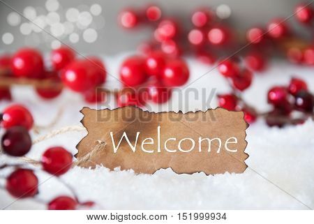 Burnt Label With English Text Welcome. Red Christmas Decoration On Snow. Cement Wall As Background With Bokeh Effect. Card For Seasons Greetings