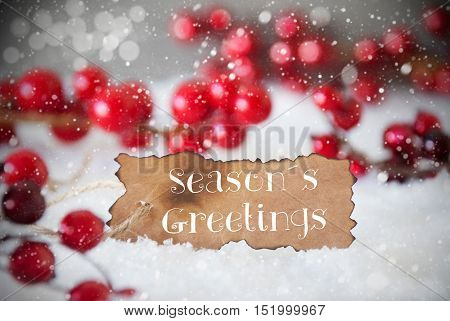Burnt Label With English Text Seasons Greetings. Red Christmas Decoration On Snow. Cement Wall As Background With Bokeh Effect And Snowflakes. Card For Seasons Greetings