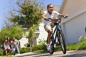 stock photo of encouraging  - A young African American family with boy child riding his bicycle and his happy excited parents giving encouragement behind him - JPG