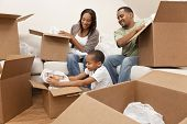 picture of crockery  - African American family parents and son unpacking boxes and moving into a new home The adults are unpacking crockery and houseware the child is unpacking a toy airplane - JPG
