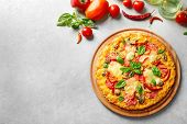 Tasty pizza with ingredients on table poster