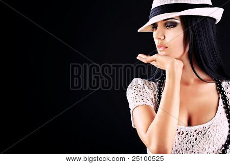 Fashion photo, a model is posing over black background