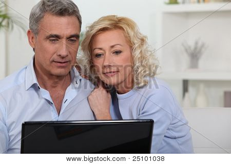 Couple looking at photos on their laptop