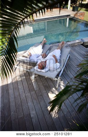 Elderly couple on sunloungers by a pool
