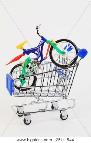 colorful plastic toy two-wheeled bicycle in purchasing cart on white background