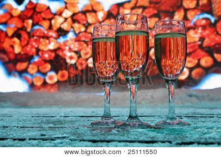 Three glasses of champagne stand near big screen, stack of wood on screen