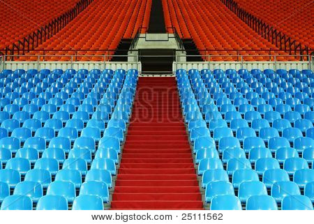 many rows of red and blue empty plastic seats at stadium; stairway