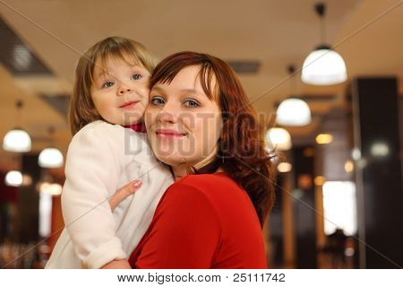 Young mother with little smiling daughter stand in empty cafe