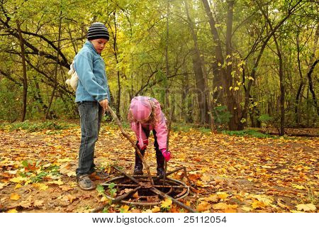 little brother and sister in autumn park poke sticks in old rusty hatch