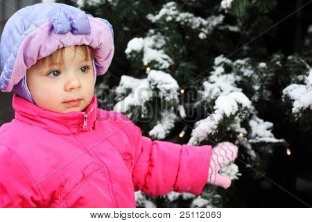 Little beautiful girl dressed pink jacket stands near green tree with snow