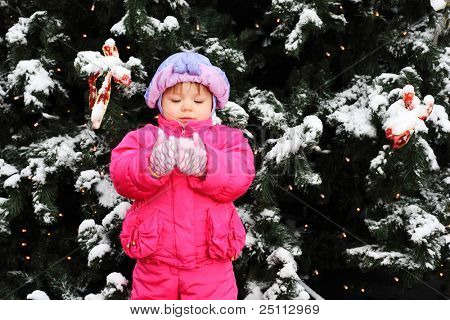 Little smiling girl dressed pink jacket stands near green tree with snow and holds snow