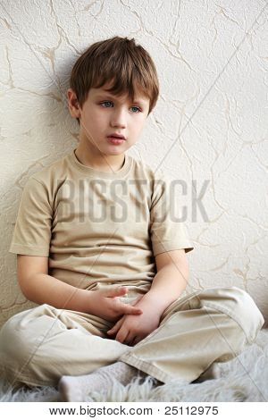 Little boy sits alone on a fleecy white rug, with his legs crossed and leaning against the wall