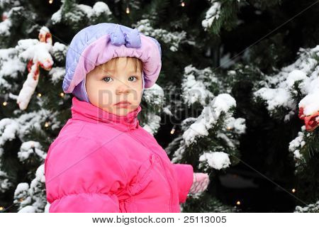 Little girl dressed pink jacket stands near green tree with snow