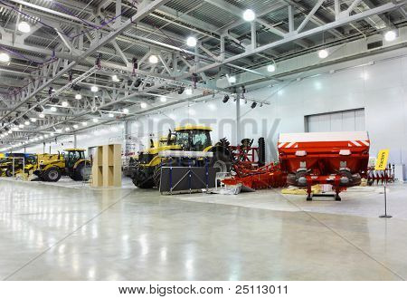 Big tractors are in room at exhibition, special agricultural machines