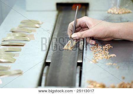 Mano femenina con artículos de pinzas, oro en la banda transportadora, foco en el dedo de puntero