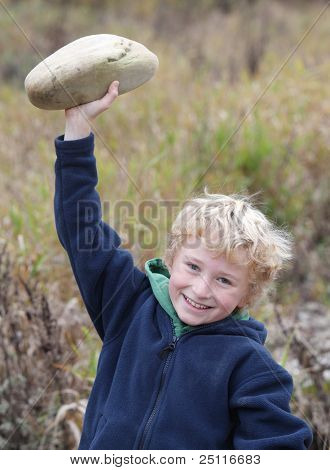 cute smiling young boy lifting a stone