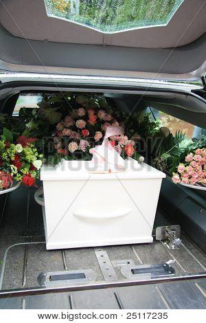 Ataúd blanco en un coche fúnebre gris