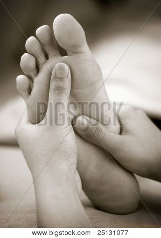 A massage therapist doing reflexology foot massage on a patient's foot