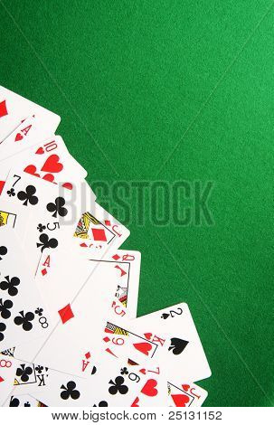 Playing cards spread out on one corner. Copy space for your design.