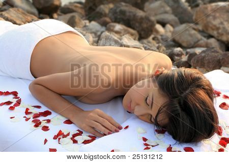 Beautiful woman getting massage & spa treatment in natural setting.