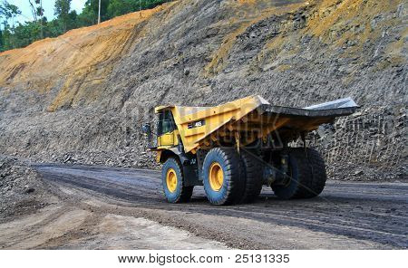 a panning shot a dump truck working on coal site
