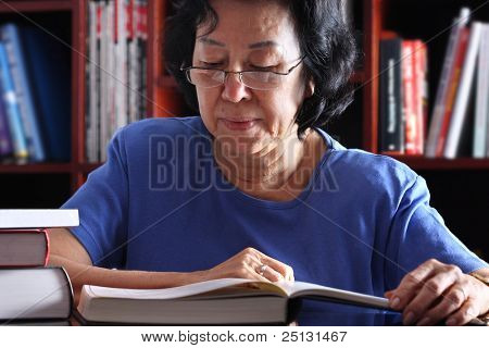 Senior Asian Woman reading in the library