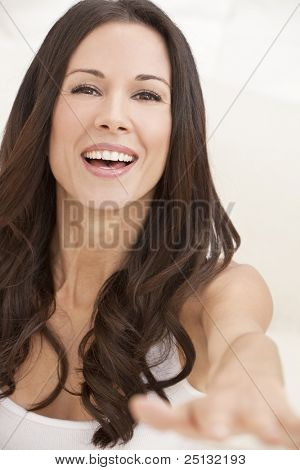 Portrait of a beautiful brunette young woman with perfect teeth smiling and reaching out