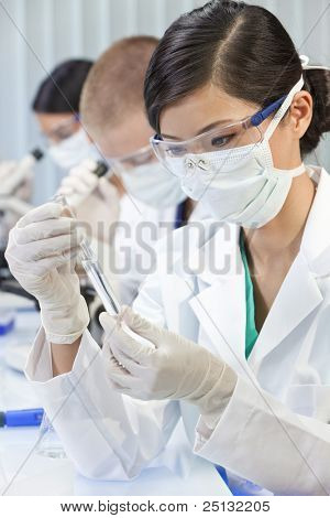 A Chinese Asian female medical or scientific researcher or doctor using looking at a test tube of clear liquid in a laboratory with her colleagues out of focus behind her.