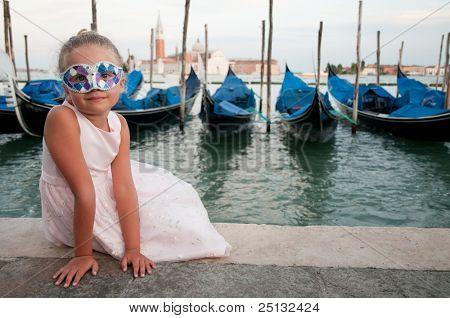 Carnival in Venice, Italy. LIttle girl with carnival mask, gondolas and San Giorgio Maggiore church in background