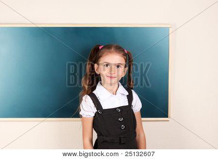 beautiful little girl standing near blackboard in the classroom