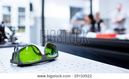 quantum optics lab - shallow DOF; selective focus on the protective goggles in the foreground (color toned image)