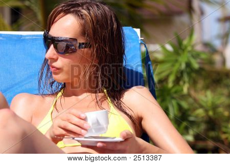 Woman Drinking Coffee By The Pool