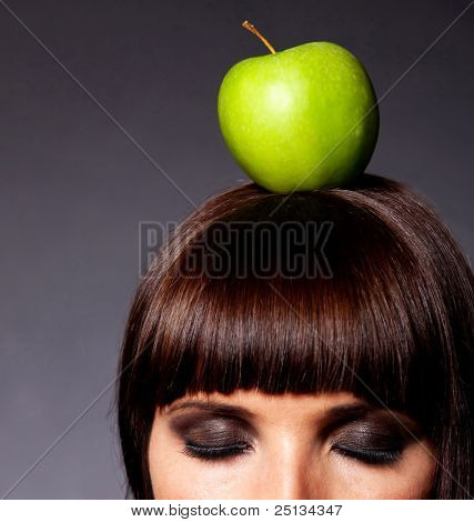 Woman with an apple on her head and closed eyes