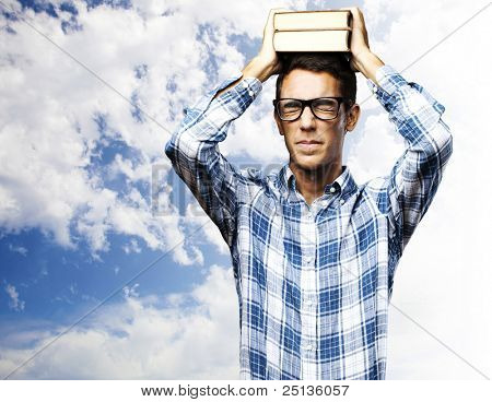portrait of young student holding heavy books on his head against a cloudy sky background