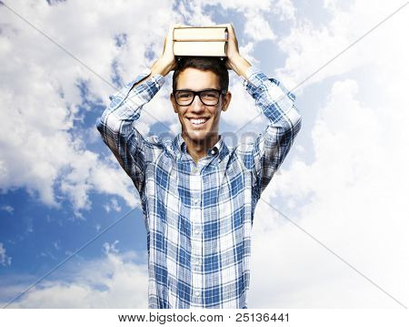 portrait of a handsome young student smiling and holding books on his head against a cloudy sky background