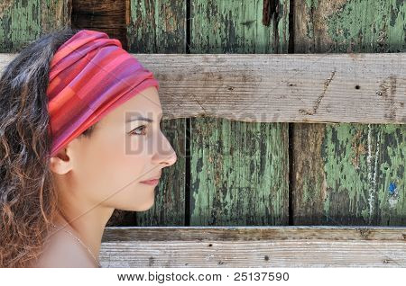 Beautiful Woman Stands In Front Of Wooden Wall
