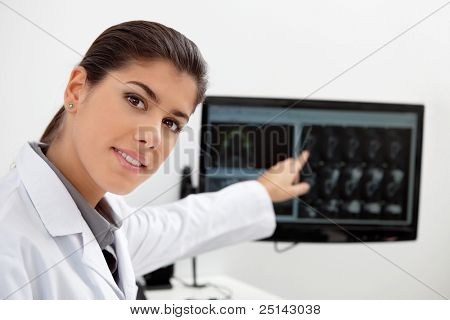 Portrait of pretty female dentist showing teeth x-ray on screen